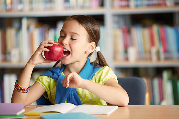 A little girl biting into a red apple, inside a library. Copywriters describe exactly how the little girl experience when eating an apple.