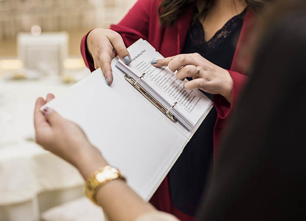 Client pointing out the checklist to a designer / copywriter in a ring folder.