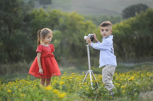 Young buy shooting a young girl model, out in the field. Will he work for exposure in lieu of payment?