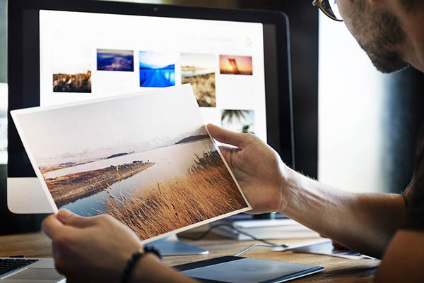 Image showing photo finishing jobs, holding up a printed image, against a monitor showing more images.
