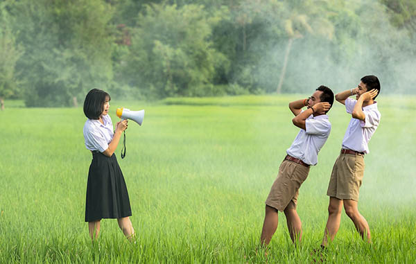 Woman using a megaphone conveying a mass message across to two men that branding works. The two men covering their ears from all the noice in an open field.