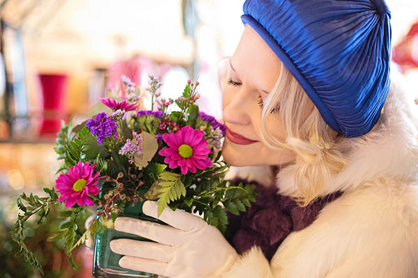 A woman holding up a pot of colourful flower arrangement, admiring it attentively.