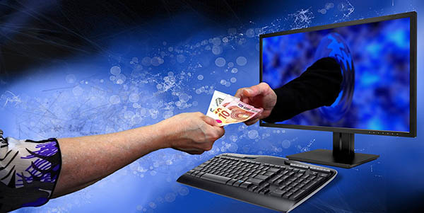 Image showing a user handing money over to an abstract person, through a computer monitor.