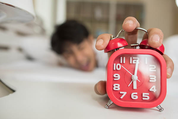 Man stretching out to reach for the alarm clock, showing that he's slept through the alarm, causing him to be late.